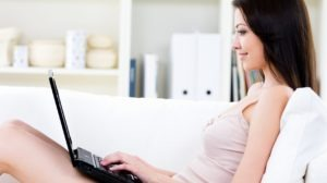 Woman with laptop on the sofa at home